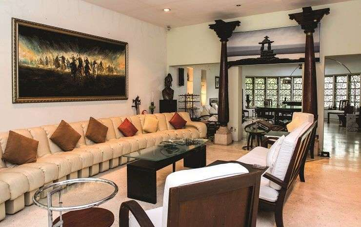 The living room at Thomas's lavish home is dominated by antiques and art and an extensive De Sede white leather sofa from Switzerland