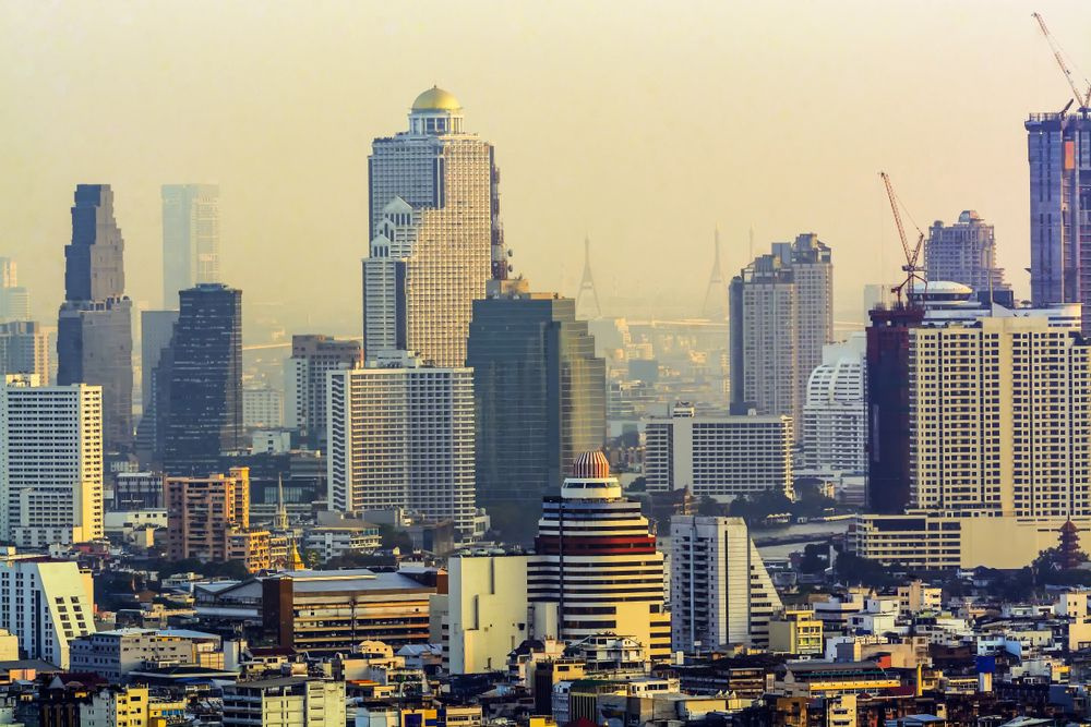 Construction cranes along the Bangkok skyline. Narupon Nimpaiboon/Shutterstock