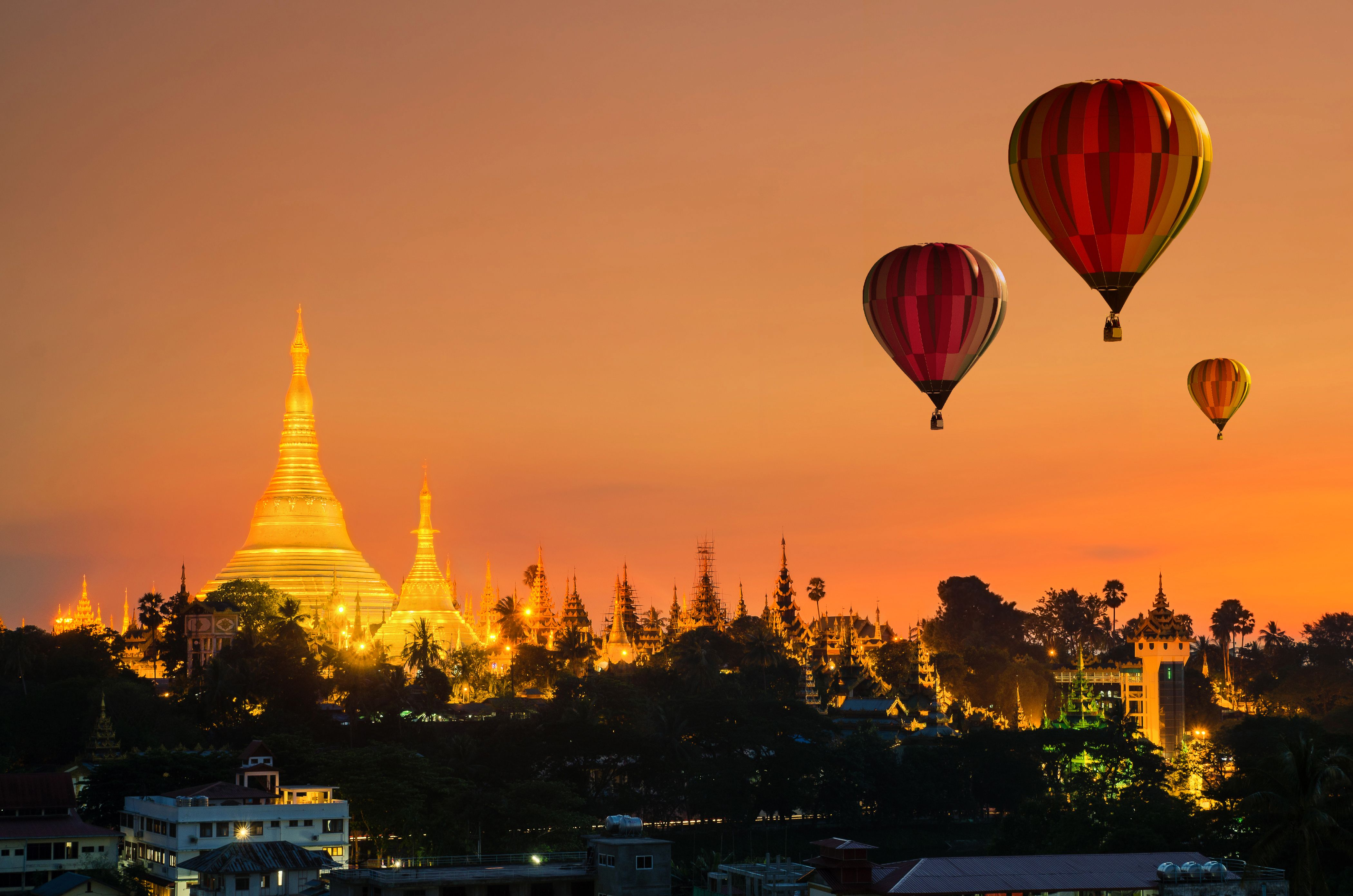 Skyline of former Myanmar capital Yangon with Shwedagon Pagoda and hot air balloons