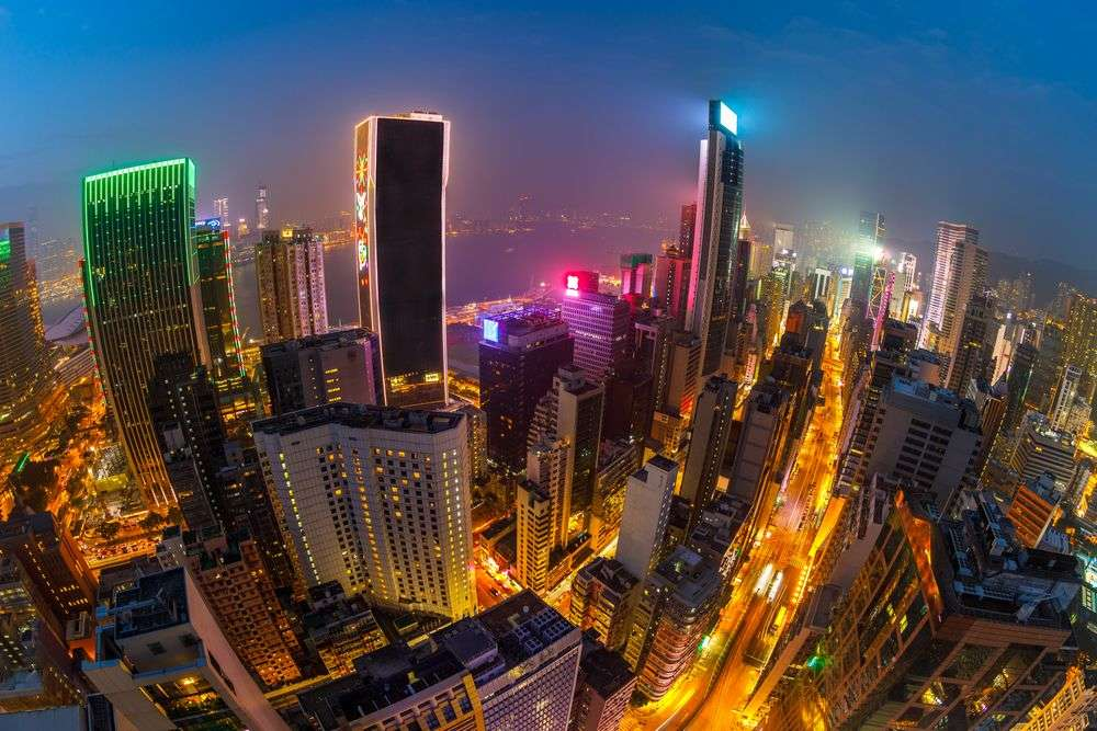 Aerial view of Hong Kong skyscrapers at night from the rooftop bar of The Hennessy in Wan Chai. Benny Marty/Shutterstock