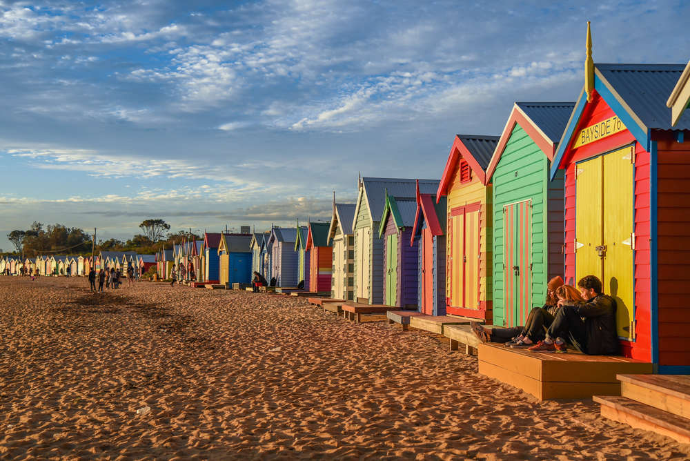 Tourists sit on deck of bathing boxes at Brighton Beach in Melbourne, Australia. Zephyr_p/Shutterstock