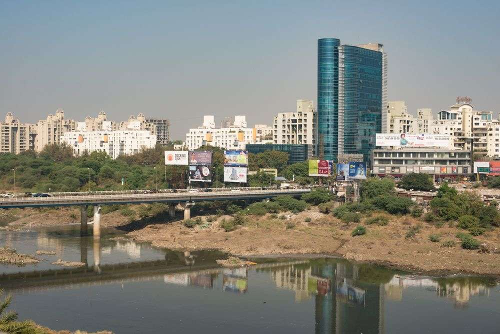 Traffic, billboards, and skyline over the Mula Mutha River in Pune, India. Jennifer Bosvert/Shutterstock