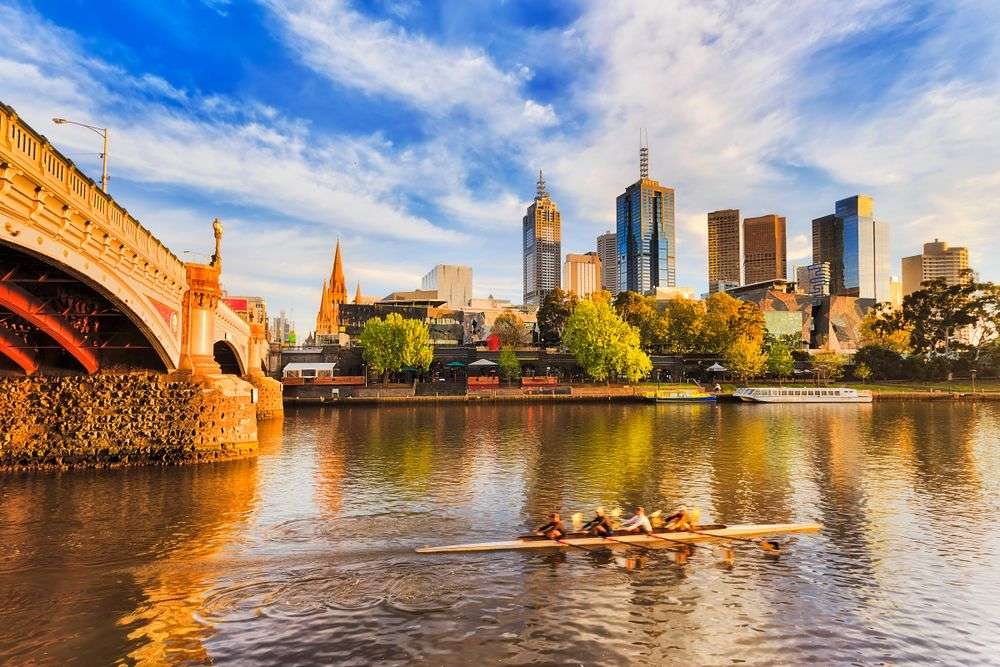 High-rises in the Melbourne CBD tower above rowers in Yarra River. Taras Vyshnya/Shutterstock