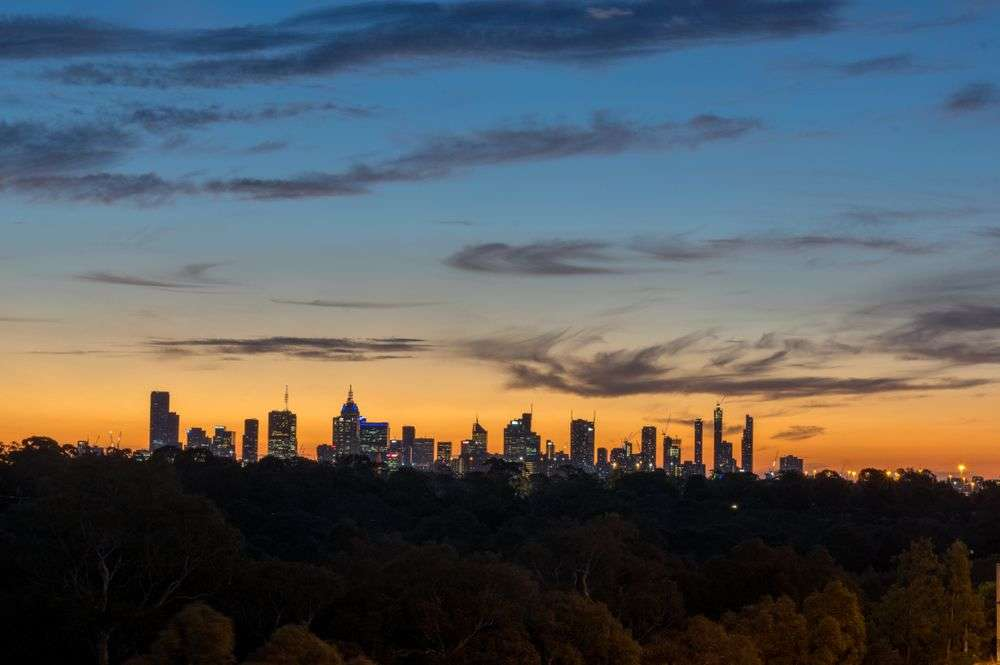 Skyline of Melbourne, Australia at dusk, looking west from the eastern suburbs on Yarra Boulevard in Kew. Nils Versemann/Shutterstock